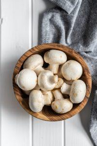 Fresh white champignon mushrooms in wooden bowl.