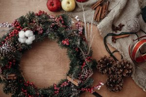 Hands making rustic christmas wreath