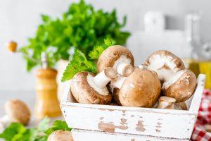 Raw mushrooms champignons on white background, cooking fresh champignons