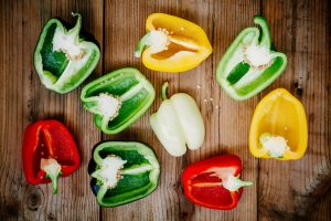 Red, green, yellow, white and black sweet bell peppers paprika on wooden background