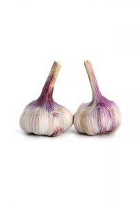 Two heads of young garlic on a clean white background.